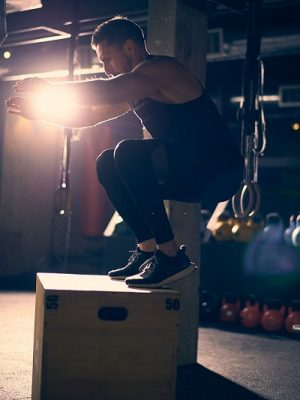 Man doing box jumps in gym
